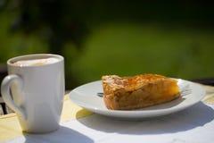 Tarte aux pommes avec le cappuccino sur la table de jardin Photographie stock libre de droits