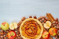Tarte aux pommes d'automne décorée de divers ingrédients - pommes coupées en tranches fraîches, noisettes, épices - anis, cannell images stock
