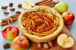 Tarte aux pommes d'automne sur le conseil en bois décoré des pommes, des noisettes et des épices fraîches - étoiles et cannelle d photo libre de droits