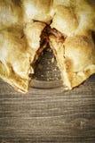 Tarte aux pommes d'or sur Barnwood rustique avec une tranche allée Photographie stock