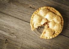 Tarte aux pommes d'or sur Barnwood rustique avec une tranche allée Images stock