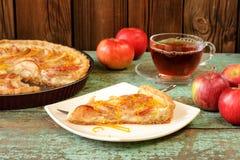 Tarte aux pommes ouverte délicieuse faite maison, thé noir et pommes rouges entières dessus Image stock