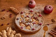 Tarte aux pommes savoureuse avec les canneberges fraîches et les noix décorées des pommes, du gingembre et de la cannelle Tarte a Images stock