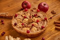 Tarte aux pommes savoureuse avec les canneberges fraîches et les noix rouges décorées de deux pommes, gingembres et cannelle Just Photos libres de droits