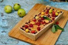 Tarte aux pommes servie avec les groseilles rouges et la framboise Images libres de droits