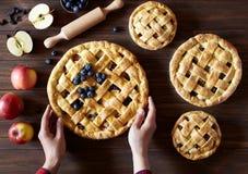 Tarte aux pommes sur la table en bois de cuisine avec les pommes et la goupille Mains dans le cadre Dessert traditionnel pour Photo stock