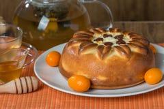 tarte avec le thé sur le fond orange Images libres de droits