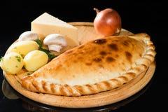 Tarte avec les pommes de terre, le fromage, les champignons et les oignons sur un verrat en bois photographie stock
