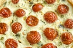 Tarte avec les tomates-cerises, le fromage et les oignons, macro de fond Image stock