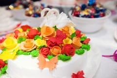Tarte blanc avec les fleurs rouges et chiffre des cygnes Photographie stock libre de droits