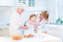 Tarte bouclé mignon de cuisson de fille d'enfant en bas âge avec des grands-mères Photo stock