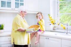 Tarte de cuisson de grand-mère et de petite fille dans la cuisine blanche Photographie stock libre de droits