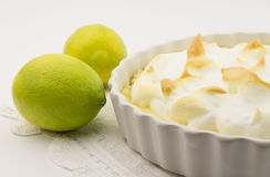 Tarte de limão e merengue e limões inteiros no branco Imagens de Stock Royalty Free