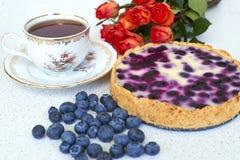 Tarte de myrtille, tasse de thé, tas des myrtilles et roses rouges sur un fond blanc Images stock
