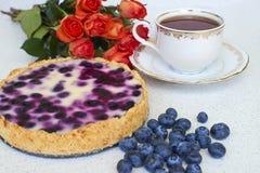 Tarte de myrtille, tasse de thé, tas des myrtilles et roses rouges sur un fond blanc - fin  Photographie stock libre de droits