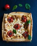 Tarte de tomates-cerises et de feta faite avec la pâte feuilletée de beurre Fond en pierre noir, vue supérieure Photographie stock libre de droits