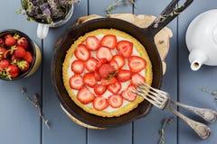 Tarte fait maison de fraise avec la crème fouettée dans la poêle de fonte Images stock