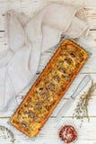 Tarte faite maison avec les champignons, le poireau, le fromage et le thym sur le fond rustique blanc Gâteau traditionnel de cass images libres de droits