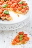 Tarte fraîchement cuite au four avec des tomates-cerises sur le blanc Photos libres de droits