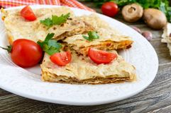 Tarte, pain pita de cocotte en terre avec le fromage de champignon et blanc et le fromage d'un plat blanc sur un fond en bois Photos stock