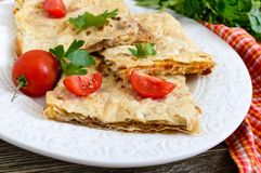 Tarte, pain pita de cocotte en terre avec le fromage de champignon et blanc et le fromage d'un plat blanc sur un fond en bois Images libres de droits