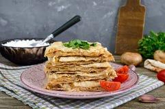 Tarte, pain pita de cocotte en terre avec le fromage de champignon et blanc et le fromage d'un plat sur un fond en bois Photographie stock
