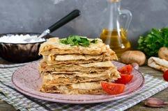Tarte, pain pita de cocotte en terre avec le fromage de champignon et blanc et le fromage d'un plat sur un fond en bois Photo libre de droits