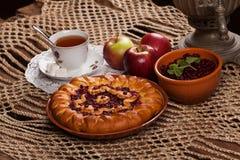 Tarte sur la table avec l'ensemble de nourriture Photographie stock libre de droits