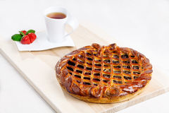 Tarte sur le bureau avec la tasse du thé et de la fraise Image stock