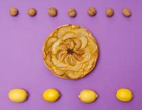 Tarte Tatin apple pear tart with fruits on purple background Stock Photos