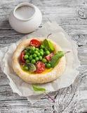 Tartelette d'oeufs de pâte feuilletée avec les pois et les tomates-cerises frais sur le conseil rustique en bois Images stock