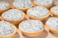 Tartelettes avec de la crème et le pavot sur la table Photographie stock libre de droits