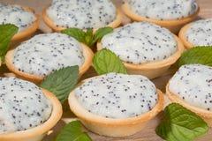 Tartelettes avec de la crème et le pavot sur la table Images stock