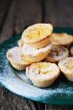 Tartelettes de citron avec du sucre en poudre d'un plat vert, dos en bois Photographie stock