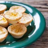 Tartelettes de citron d'un plat vert, fond en bois Images libres de droits