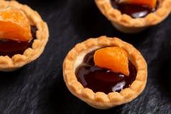 Tartelettes douces avec du chocolat et des tranches de mandarine sur un plat d'ardoise naturelle pour servir, plan rapproché photographie stock libre de droits