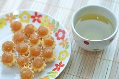 Tartes d'ananas et une tasse de thé vert Photographie stock