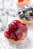 Tartes de fruit avec les baies et la fraise sur la fin légère de fond  Dessert et friandise délicieux Photo stock