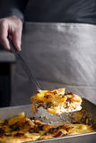 Tartiflette in the backing tray with slice on the spatula vertical Stock Image