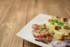 Tartiflette con tocino, las patatas y el queso rayados Foto de archivo libre de regalías