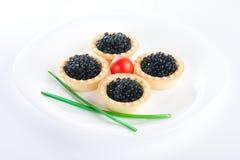 Tartlet avec le caviar noir sur un champ de cablage à couches multiples blanc images stock
