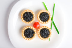 Tartlet avec le caviar noir sur un champ de cablage à couches multiples blanc photo stock