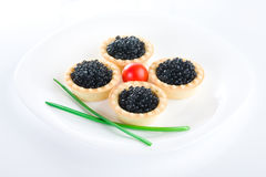 Tartlet with black caviar on a white platter. Decorated with cherry tomatoes and green onions stock images