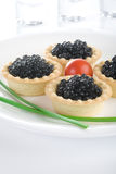 Tartlet with black caviar on a white platter. Decorated with cherry tomatoes and green onions royalty free stock photo