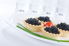 Tartlet with black caviar on a white platter. Decorated with cherry tomatoes and green onions stock photo