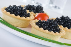 Tartlet with black caviar on a white platter. Decorated with cherry tomatoes and green onions royalty free stock photography
