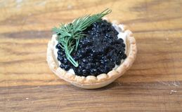 Tartlet with butter and black caviar stock photography