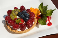 Tartlet with cheese cream, wild berries and kiwi Royalty Free Stock Image