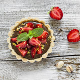 Tartlet with chocolate cream, strawberries and pistachios Stock Photo