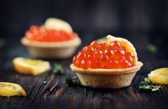 Tartlet con el primer de color salmón del caviar Bocados con el caviar de la trucha Fotografía de archivo